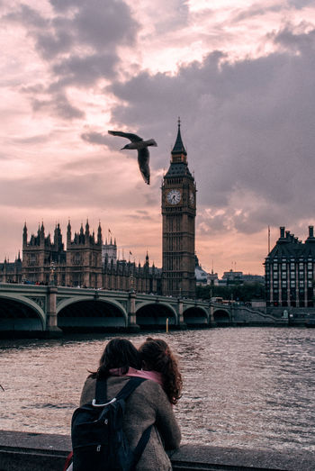 Mother and daughter by thames river against big ben during sunset