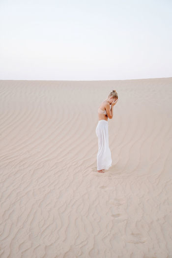 Woman in the sand dune hiding her face with hands