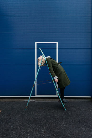 Side view full length of woman leaning on ladder by blue wall