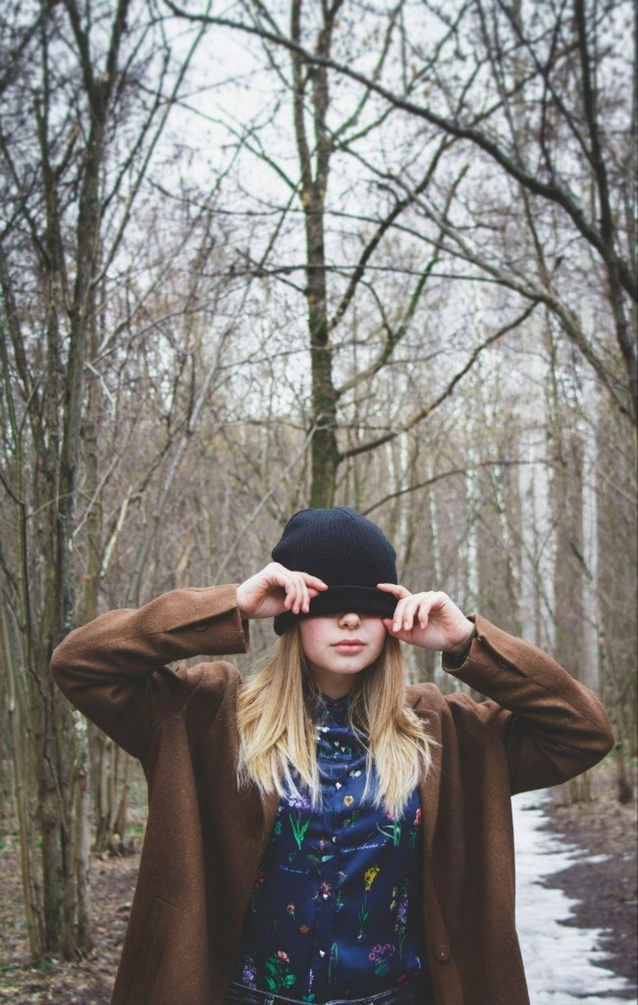 Beautiful young woman with hat over eyes against tree trunks