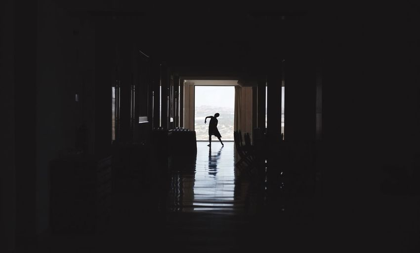 Silhouette Of Person Dancing In Corridor
