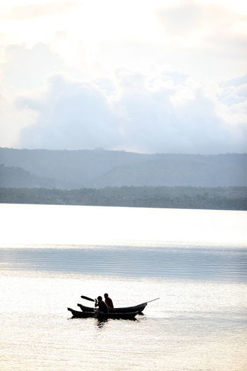 People sailing on rowboats in river against sky