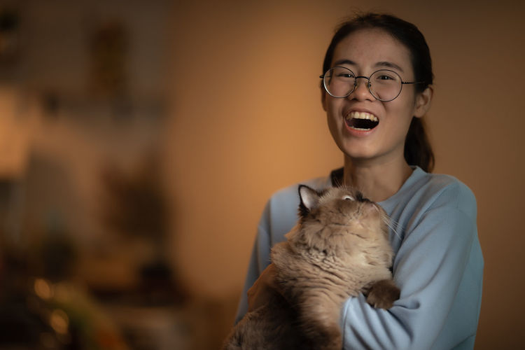 Portrait of a young woman with cat