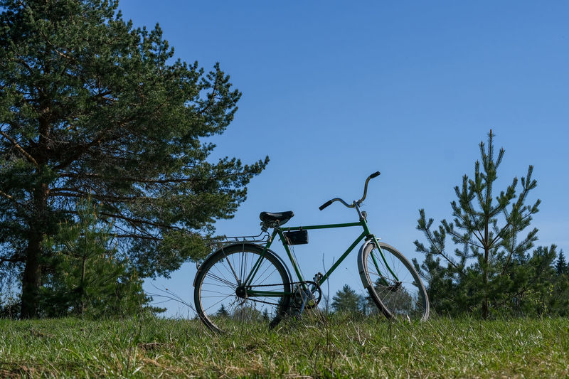 Plant Bicycle Tree Sky Land Vehicle Transportation Nature Grass Mode Of Transportation Field Clear Sky Land Blue No People Day Green Color Stationary Outdoors Growth Travel Wheel
