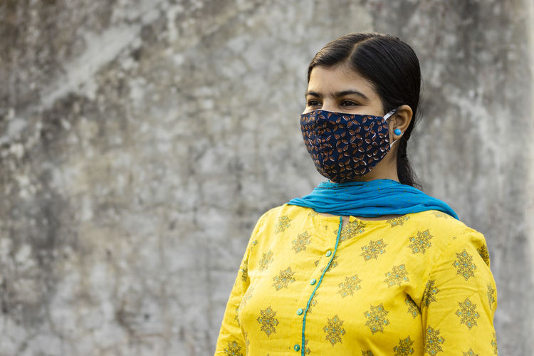 An indian woman wearing homemade cotton nose mask and looking right during corona virus pandemic