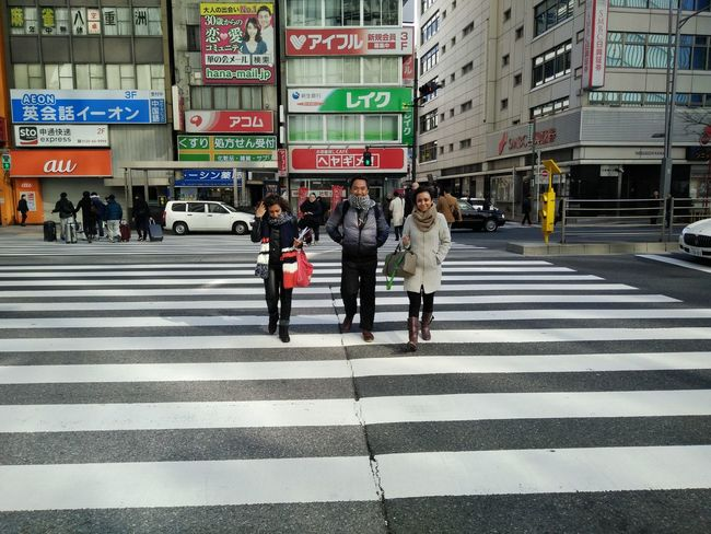 Three Indonesian people crossing the street in Tokyo Architecture Built Structure City City Life City Street Crosswalk Full Length Group Of People Information Sign Leisure Activity Lifestyles Medium Group Of People Men Outdoors Pedestrian Road Road Marking Road Sign Street Zebra Crossing