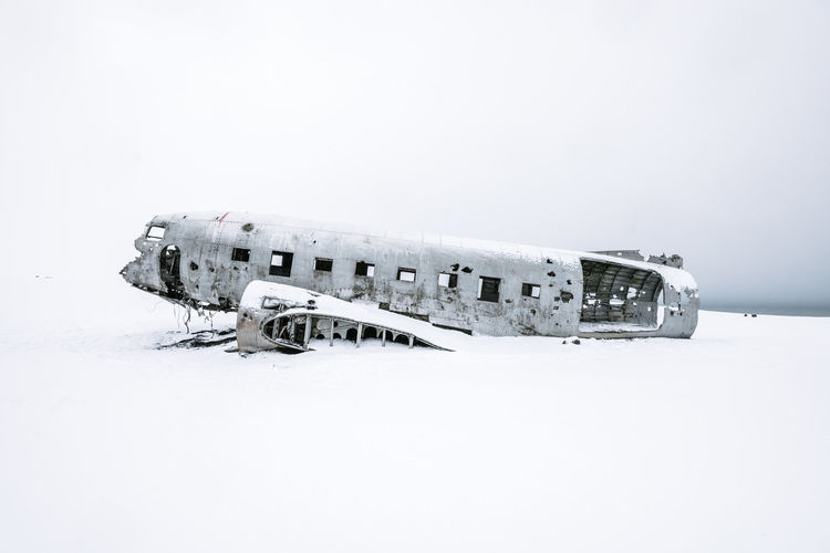 Abandoned Airplane On Snow Covered Landscape Against Clear Sky