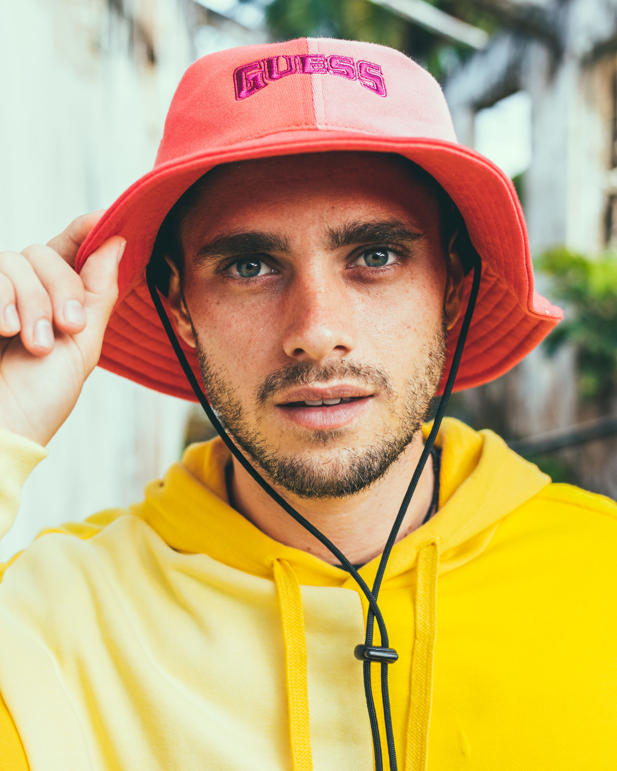 portrait, one person, adult, clothing, headshot, yellow, looking at camera, person, sports, men, beard, young adult, hat, jockey, front view, facial hair, lifestyles, day, sports clothing, outdoors, close-up, headwear, focus on foreground, athlete, helmet, occupation, protection, city, human face, leisure activity