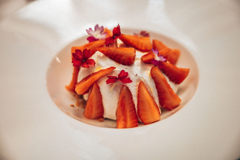 High angle view of orange fruit in plate on table