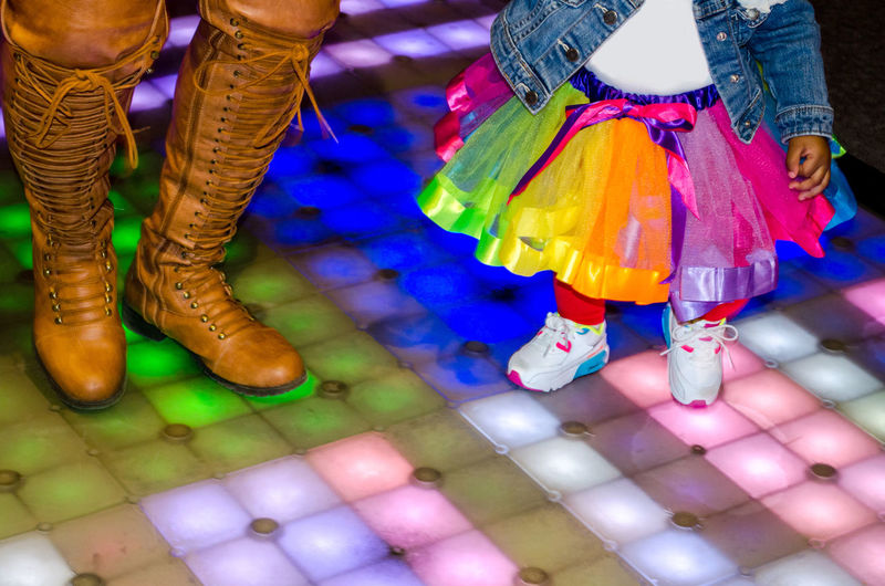 Low section of person with girl standing on dance floor