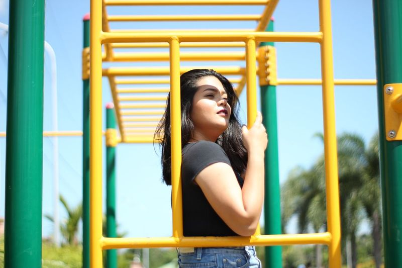 Young woman looking away while standing on jungle gym