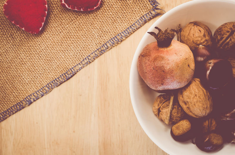 High angle view of pomegranate and walnut in bowl on table