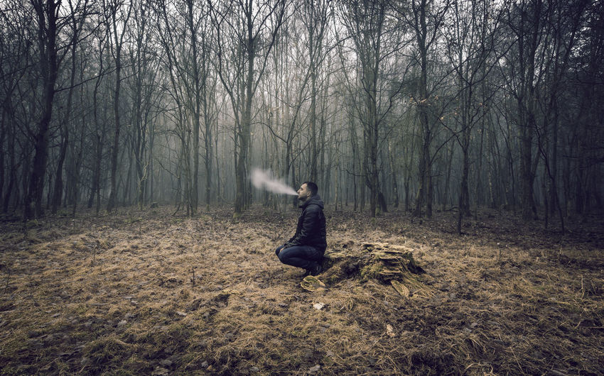 Man Smoking In Forest During Winter