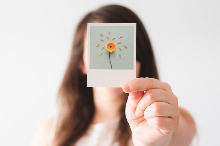 Close-up of woman holding picture against white background