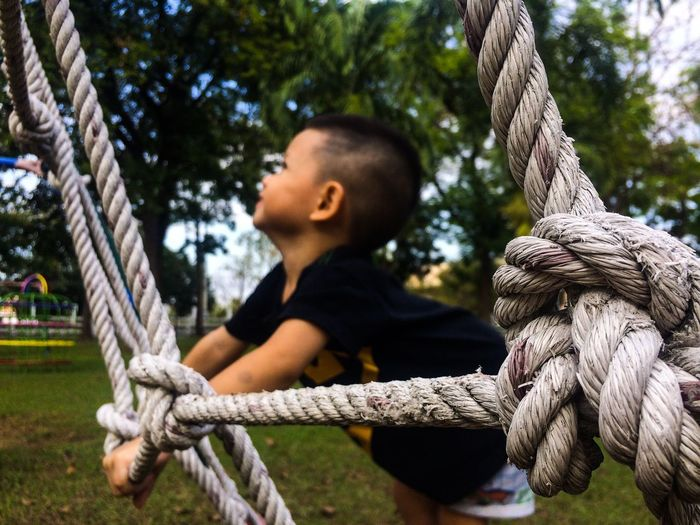 Side view of boy holding rope while playing in park