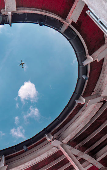 Low angle view of airplane flying seen through built structure against sky