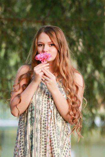 Portrait of beautiful woman holding flower