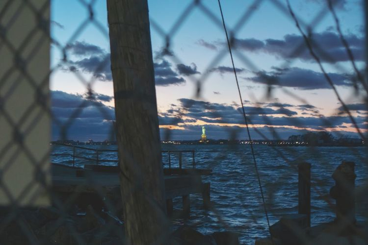 liberty? Statue Of Liberty International Landmark Tourism Tourist Attraction  Politics And Government Sunset Night Water Liberty NYC Fence Chainlink Fence Brooklyn Urban Landscape Famous Place Famous Places Illuminated Clouds Sundown Sunset_collection City Tree Sky Cloud - Sky Tall - High My Best Photo