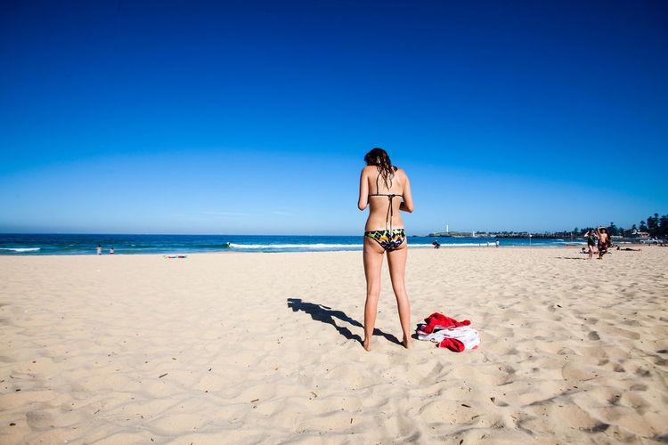Rear View Of Woman Wearing Bikini At Beach Against Clear Sky