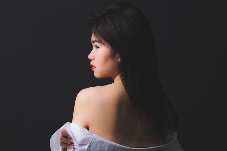 Sensuous woman undressing against black background