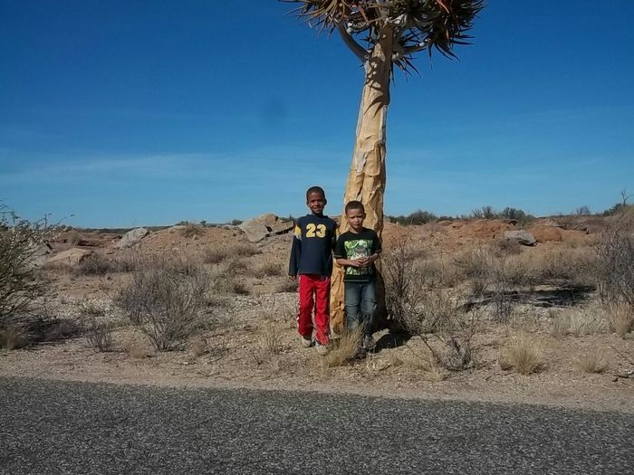 Faces In Places Hanging Out Rocks Tree And Sky Blue Sky The Kalahari Children Of The World Happy Children Children Photography Children Of The Kalahari