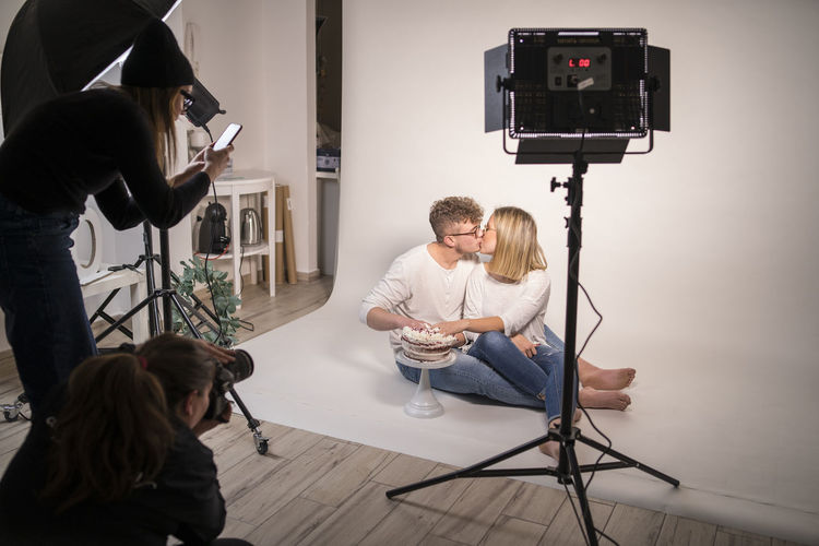 Man photographing woman sitting at home