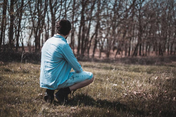 Full length of man crouching on field