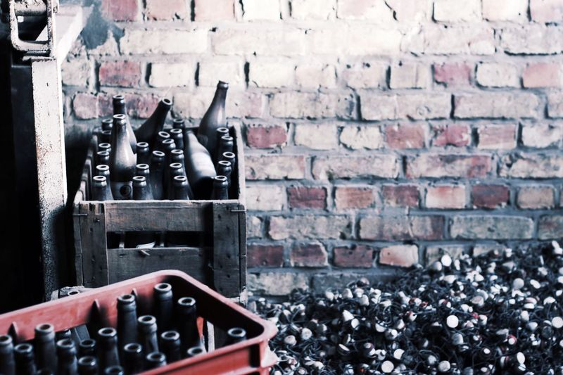 High Angle View Of Wine Bottles By Brick Wall