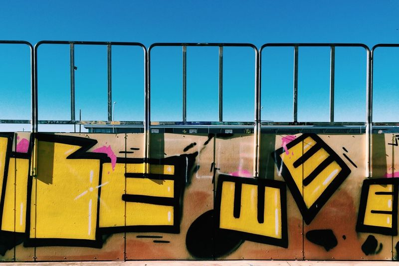 Close-up of graffiti on wall against clear blue sky