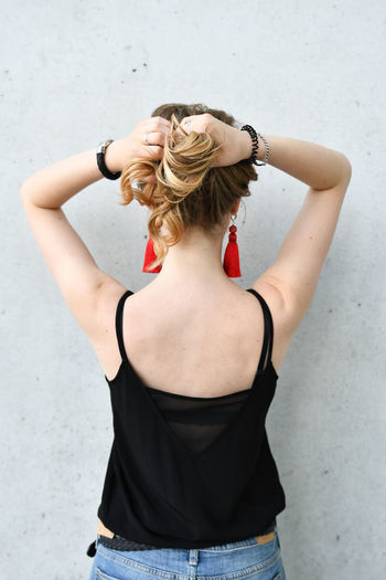 One Person Hair Lifestyles Standing Women Hairstyle Real People Leisure Activity Hand In Hair Young Women Beauty Waist Up Young Adult Wall - Building Feature Casual Clothing Three Quarter Length Long Hair Beautiful Woman Arms Raised Human Arm Hands Behind Head Top - Garment Fashion