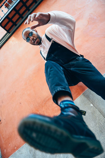 Young black man man kicking towards the ground. Lifestyle concept. One Person Real People Men Casual Clothing Lifestyles High Angle View Leisure Activity Shoe Low Section Full Length Day Outdoors Architecture Males  Built Structure Sitting Clothing Building Exterior Human Leg Jeans