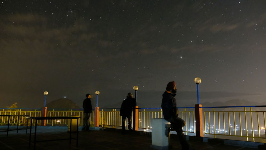 People standing by railing against sky at night