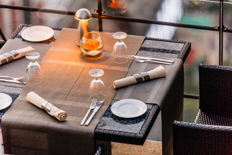 Outdoor dinning table set including plate, cutlery, napkin and wine glass. Absence Business Chair Drinking Glass Focus On Foreground Food Food And Drink Furniture Glass Glass - Material High Angle View Household Equipment Indoors  No People Restaurant Seat Setting Still Life Table Transparent Wood - Material