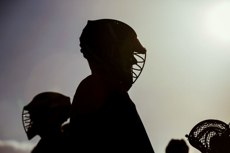 Silhouette Man Wearing Sports Clothing And Helmet Standing Against Sky During Sunset