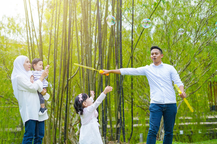 Playful family spending time together at park. Group Of People Men Standing Togetherness Plant Women Young Adult Adult Human Body Part Nature Tree Young Men Three Quarter Length Young Women Males  Casual Clothing Day Family Land Limb Human Limb Human Arm Body Part Son Outdoors