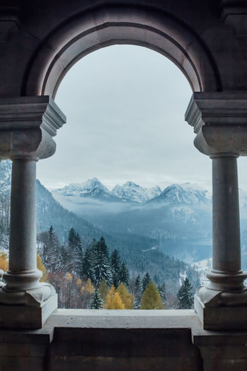 SCHWANGAU, BAVARIA, GERMANY - NOVEMBER 17, 2017: Beautiful landscape and Schwangau village and Alpsee lake seen from the balcony of Neuschwanstein castle in Bavaria, Germany Mountain Nature Sky Beauty In Nature No People Cold Temperature Scenics - Nature Winter Architecture Built Structure Day Snow Mountain Range Fog Arch Plant Outdoors Tranquil Scene Tree Architectural Column Snowcapped Mountain Neuschwanstein Castle Balkon Through The Window My Best Photo