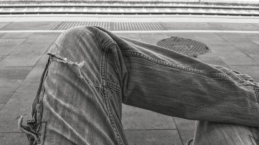 Midsection image of man sitting at railroad station platform
