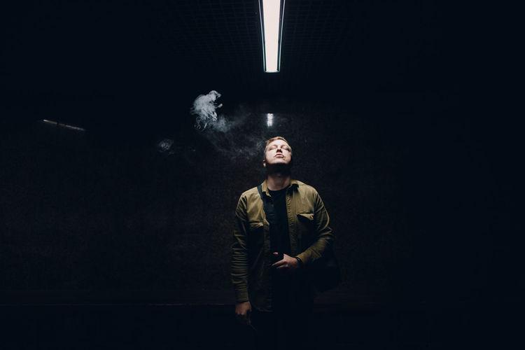 Digital composite image of man smoking cigarette against black background