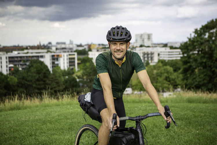 Portrait of man riding bicycle on grass