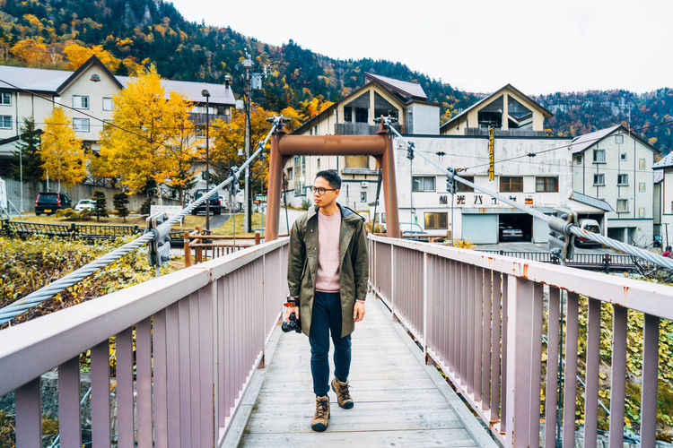 Daisetsuzan Architecture One Person Real People Full Length Building Exterior Young Adult Looking At Camera Built Structure Standing Lifestyles Casual Clothing Portrait Railing Leisure Activity Front View Day Nature Tree Building Outdoors Footbridge