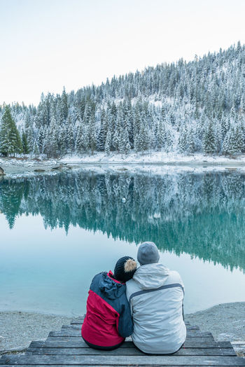Rear View Of Couple Sitting At Lake Against Sky