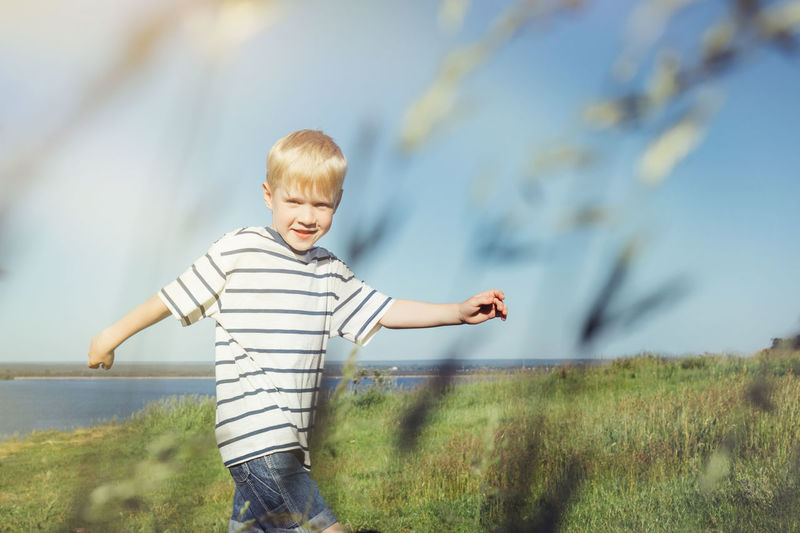 Portrait Of Smiling Boy Standing On Grassy Field