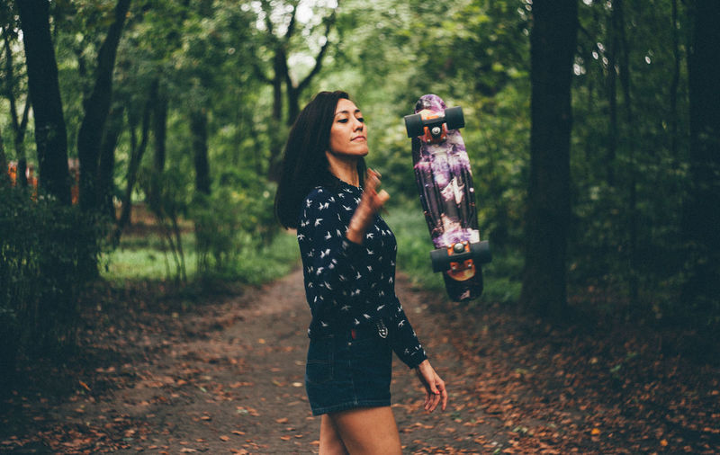 Young woman with skateboard at park