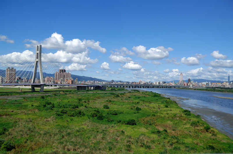Bridge over field against sky in city