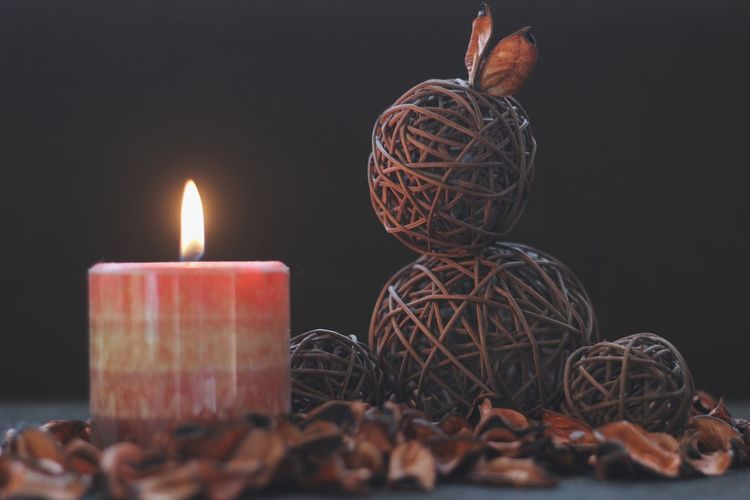Close-Up Of Lit Candle By Decoration And Dry Leaves On Table