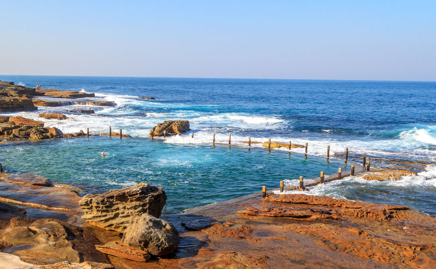 Mahon Rock Pool from a distance Swimming Beach Beauty In Nature Blue Clear Sky Day Groyne Horizon Over Water Mahon Pool Nature No People Outdoors Pool Rock - Object Rock Pools Scenics Sea Sky Swimming Pool Tranquil Scene Tranquility Travel Destinations Vacations Water Wave