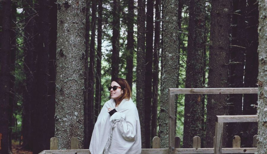Young woman wearing shawl while standing by trees in forest