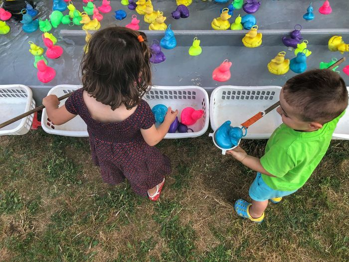 High angle view of siblings playing with rubber ducks