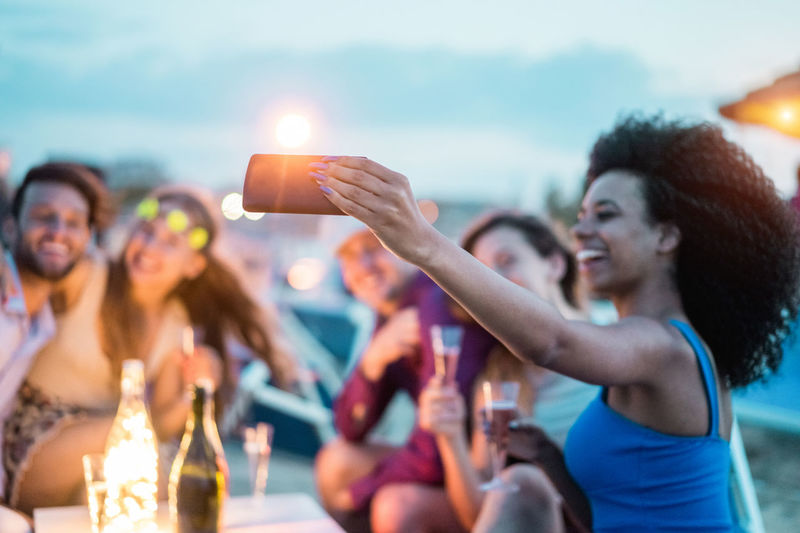 Smiling woman taking selfie with friends at dusk