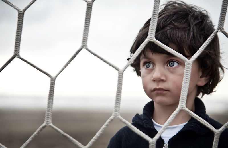 Close-up of cute boy looking through net
